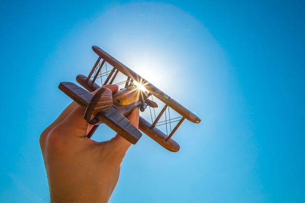 The hand launch a wood plane on the background of the sun