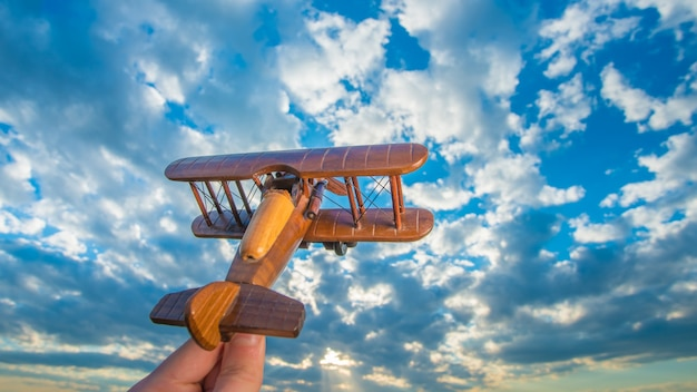 The hand launch wooden plane on the background of a blue sky