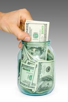 Рука кладет доллары в банку