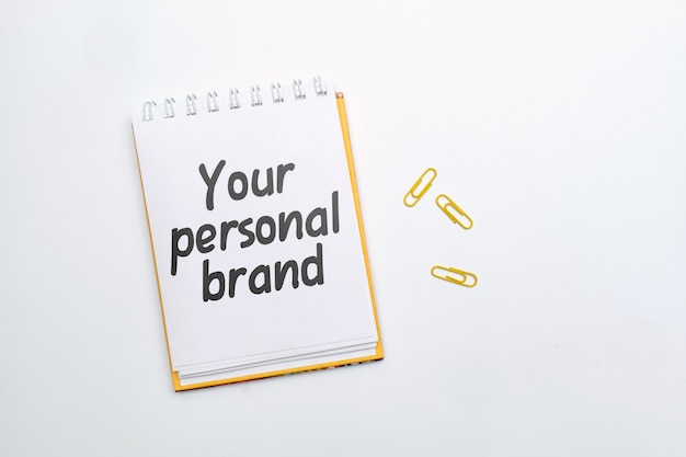 Hand lettering in a notebook your personal brand on a white background.