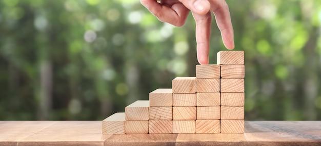 Рука похожа на человека, подходящего к игрушечной лестнице из дерева