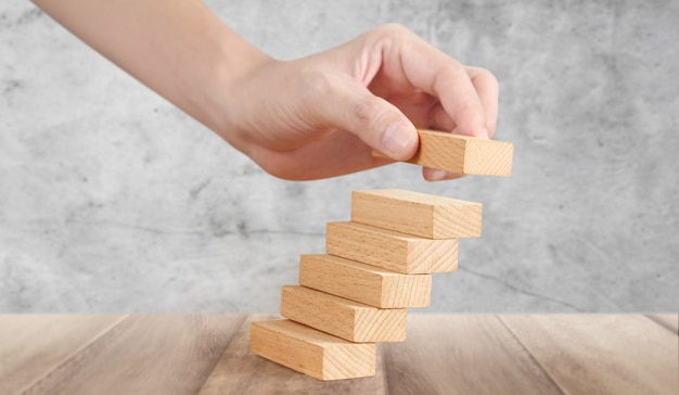 Hand liken person stepping up wood block stacking as step stair