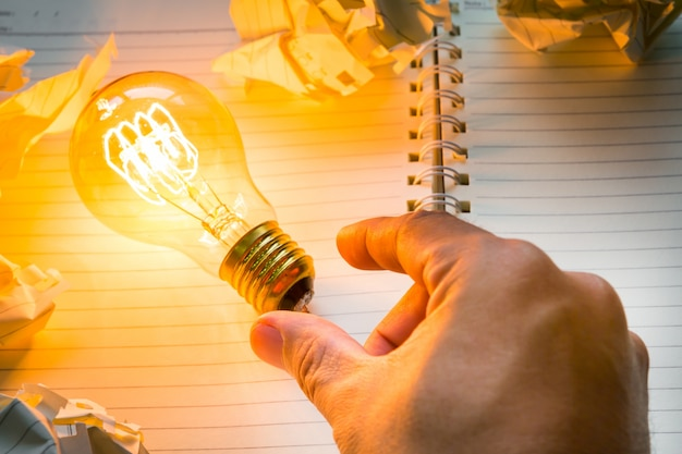 Hand next to a lit light bulb Free Photo