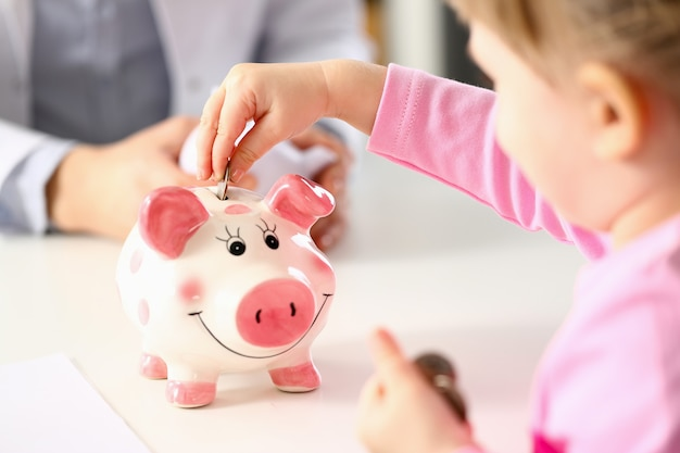 Hand of little girl putting coins in funny piggy bank pin slot
