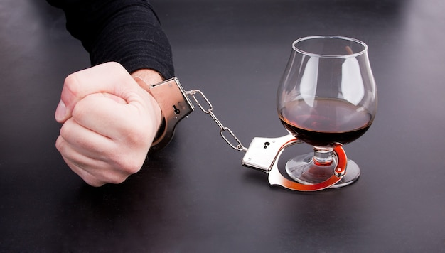 Рука прижата к стакану с алкоголем