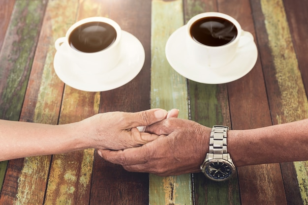 Hand love of ole couple in coffee shop