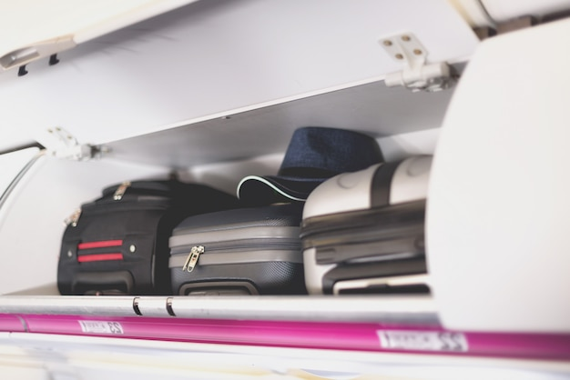 Hand-luggage compartment with suitcases in airplane.