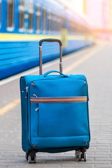 Hand luggage on the platform near the train carriage. blue suitcase for travel and leisure. vertical photo