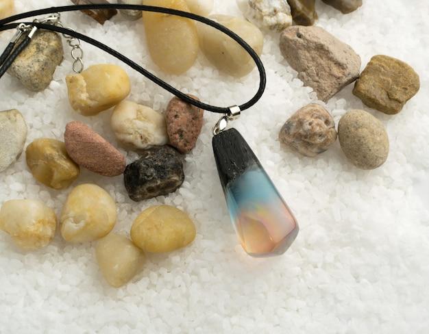 天然石と白いクリスタルの背景にスモーキーピンクとブルーの手作りペンダント。エポキシ樹脂と木材で作られた宝石