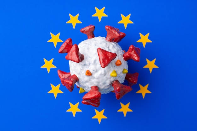 유럽 연합 국기 중앙에 손으로 만든 covid-19 모델