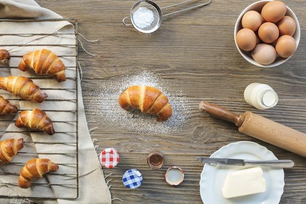 手作りのクロワッサンと木製のテーブルの上にそれを作る食材