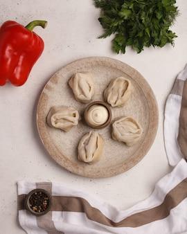 손으로 만든 만두. 만두 요리하기. 허브와 야채로 만든 만두