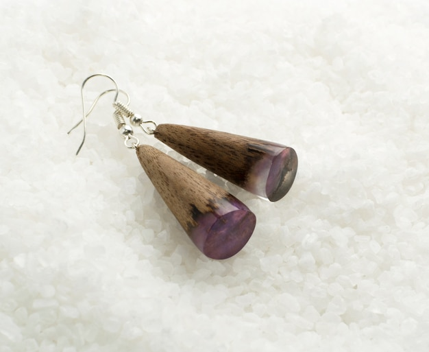 Hand made earrings on white crystal background. bijouterie made of epoxy resin and wood