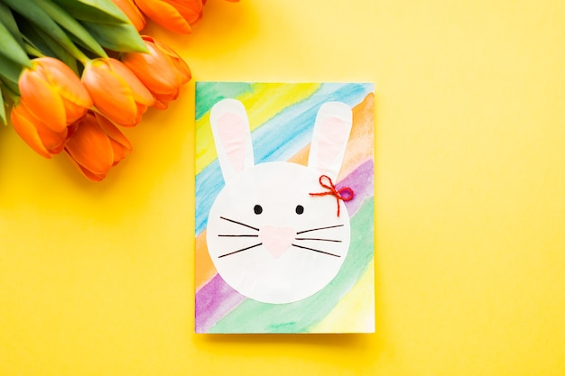 Hand-made easter card and orange tulips on yellow background.