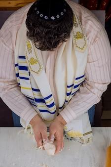 Плоская кошерная маца ручной работы в ортодоксальном еврейском мужчине готовится к выпечке к еврейскому празднику песах