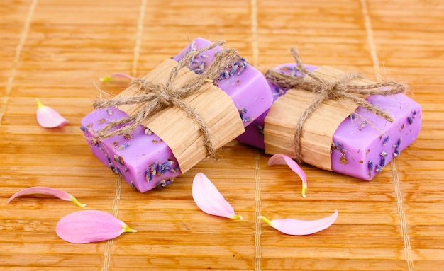Hand-made lavender soaps on wooden mat