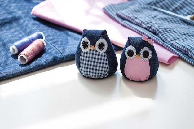 Hand made owls with materials on the table
