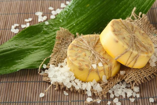 회색 대나무 매트에 손으로 만든 비누, 바다 소금 및 잎