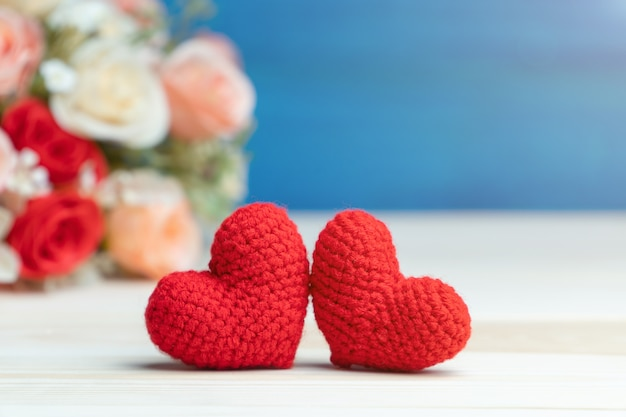 Рука делает две пряжи красное сердце перед розовым букетом цветов на деревянном столе и синем фоне