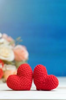 Рука делает две пряжи красное сердце перед розовым букетом на деревянном столе