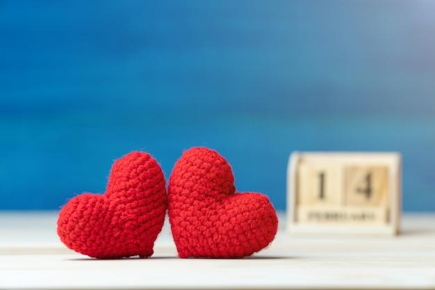 Рука делает две пряжи красное сердце перед деревянным календарем