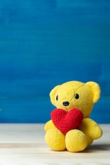 黄色いテディベアに手で作った糸の赤いハート