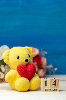 Hand make yarn red heart put on yellow teddy bear beside wooden block calendar