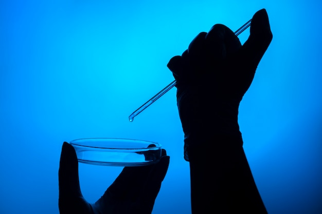 Рука делает тест в лаборатории с чашкой петри и пипеткой