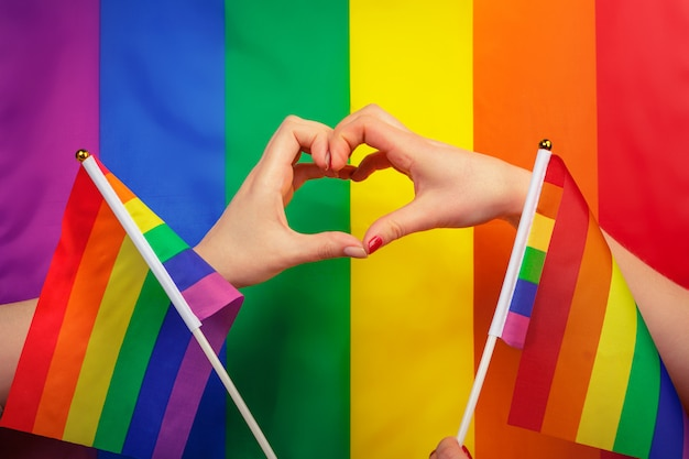 Hand making a heart sign with gay pride lgbt rainbow flag