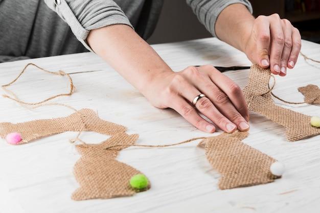 테이블에 황마 옷에서 토끼 모양 깃발 천을 만드는 손