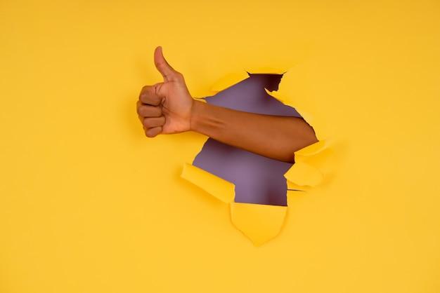 引き裂かれた紙の壁を介して手で親指を立てるジェスチャーを作る手。