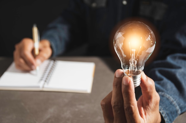 Hand of male holding a light bulb and copy space for accounting