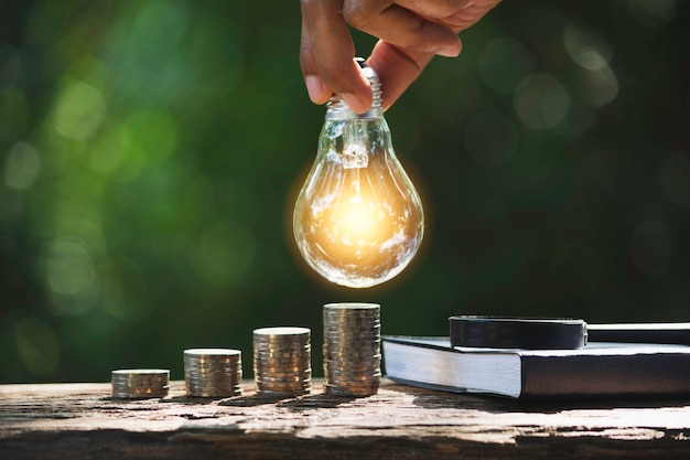 Hand of male holding a light bulb with stack of coins and copy space for accounting, ideas and creative concept.