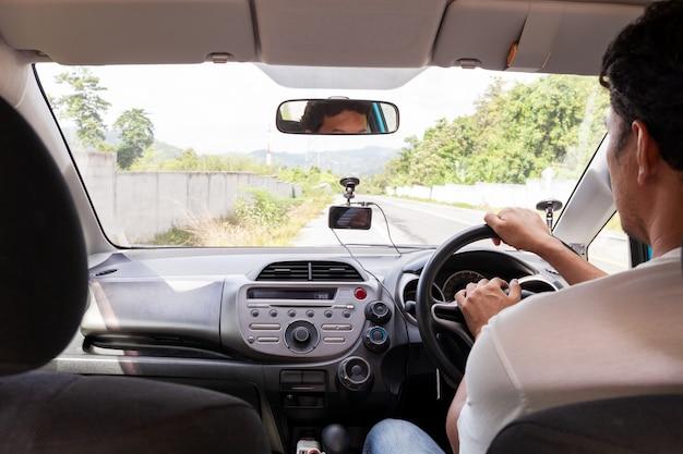 Рука мужчины, держащего руль, чтобы вести машину на асфальтовой дороге.