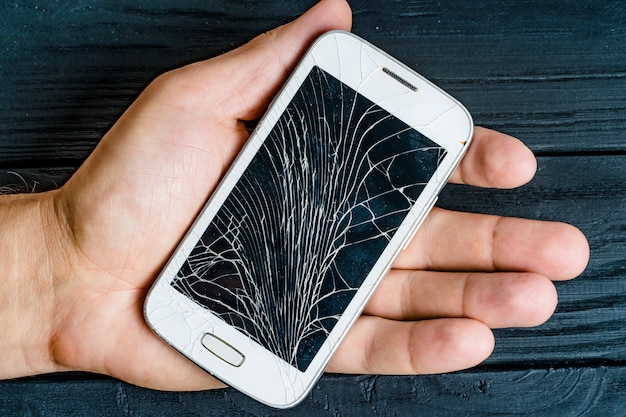 Hand of a male holding white smartphone with damaged glass screen indoors.