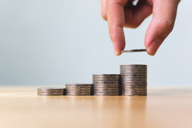 Hand of male putting coins stack step growing growth value
