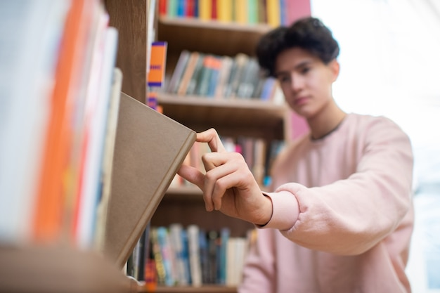 Hand of male teenager in pink sweatshirt taking book in brown cover from shelf while visiting college library after lessons