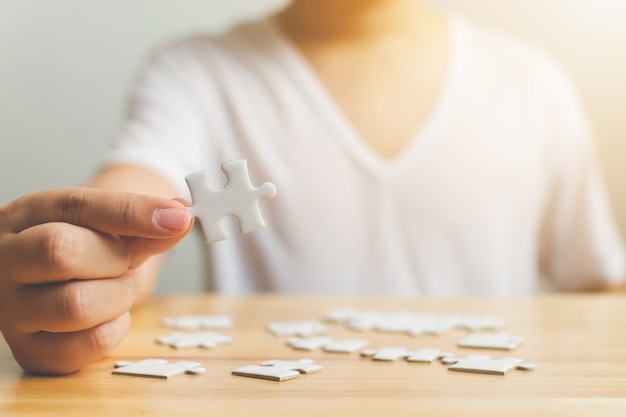 Hand of male trying to connect pieces of white jigsaw puzzle on wooden table