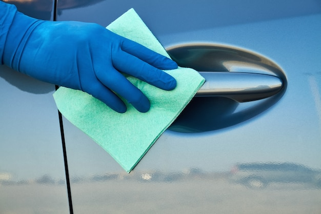Hand of man in blue protective glove is wiping with a cloth an exterior handle of car door. coronavirus or covid-19 protection.