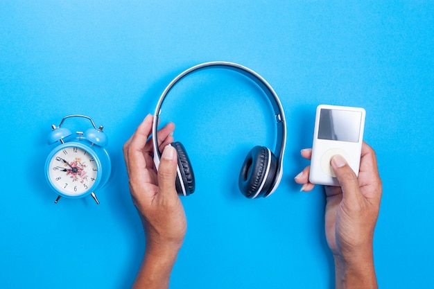 Hand man hold wireless headphone, media player, blue alarm clock on blue paper background