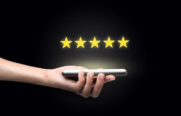 Рука мужчина держит смартфон с пятью звездами отличный рейтинг