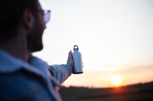 Hand of man holding aluminium bottle for water, on background of sunset