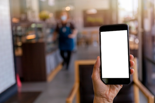 Hand man holding black mobile phone with blank white screen with blur coffee shop scene