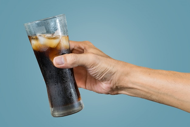 Hand of a man holding a cola glass with ices isolated on blue
