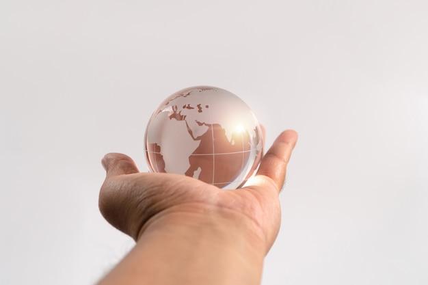 孤立した背景にガラス地球を保持している手マン。