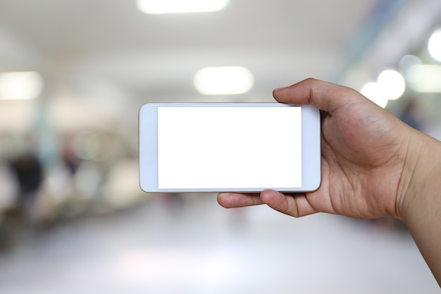 Hand of a man holding smartphone device on blur hospital.