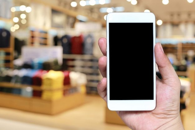 Hand of a man holding smartphone device in the blur shopping mall.