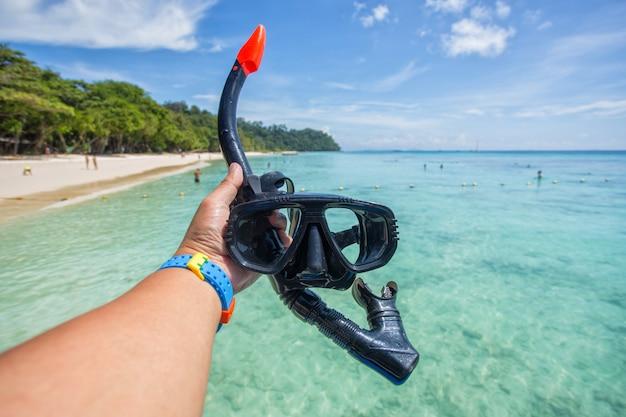 Hand man holding snorkel goggles