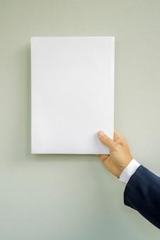 白い紙をモックアップしている黒いスーツの手の男。