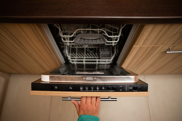 Hand of man opening dishwasher in apartment